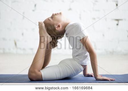 Girl child practicing yoga on blue mat, stretching in raja bhudjangasana exercise, King Cobra pose, working out wearing sportswear, t-shirt, pants, indoor full length, white loft studio background