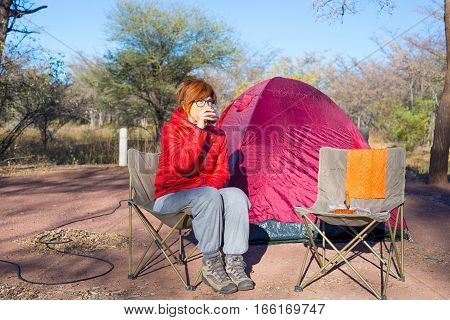 Woman Drinking Hot Coffee Mug While Relaxing In Camping Site. Tent, Chairs And Camping Gears. Outdoo