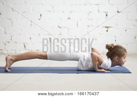 Happy girl child practicing yoga, standing in chaturanga dandasana exercise, four limbed staff pose, Push ups, working out wearing sportswear, indoor full length, white studio loft background
