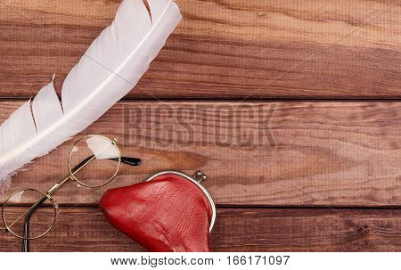 Old glasses near feather and vintage purse on wooden background with copy space