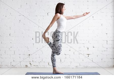 Beautiful young model working out in loft interior, doing stretching warmup before yoga exercise on mat, preparation for lord of the dance pose. Sport active lifestyle concept. Full length, side view