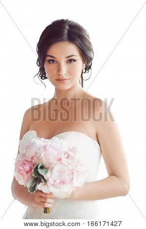 Beauty portrait of bride wearing wedding dress with feathers with luxury delight make-up and hairstyle, studio indoor photo. Young attractive multi-racial Asian Caucasian model with pink bouquet of flowers. Smiling beautiful young woman like a bride isola
