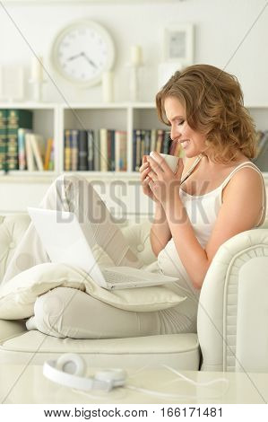 young beautiful woman using  laptop and drinking tea sitting on sofa  at home