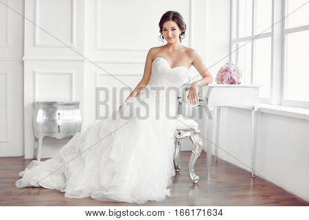 Wedding preparation. Beautiful young bride in white wedding dress indoors. Luxuty model sitting on chair with brides bouquet like at home in studio room with big window. Girl shows wedding fashion in decorated bright chic interior, high key.