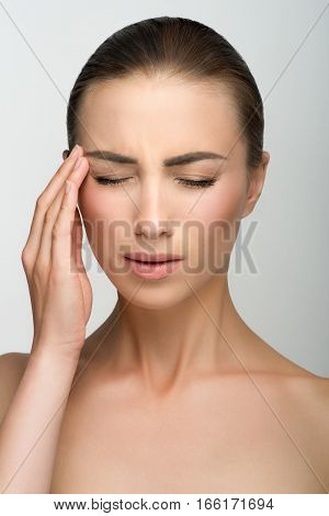 Young girl with big eyes and dark eyebrows, with naked shoulders, looking down, a model with light nude make-up, gray studio background, beauty photo, close up, headache, severe pain