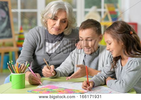 Portrait of smiling grandmother with kids drawing together