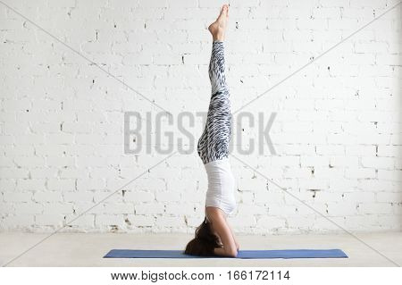 Young attractive woman practicing yoga, standing in salamba sirsasana exercise, headstand pose, working out wearing sportswear, pants, top, indoor full length, white loft studio background