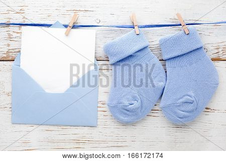 Small boy blue socks, blank card in evelop on white wooden background.