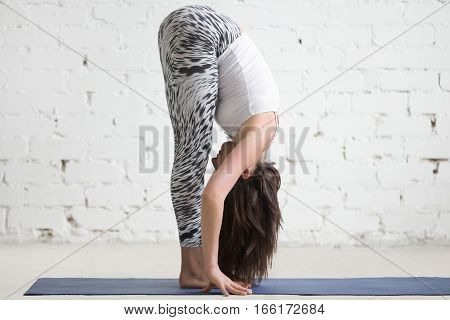Young attractive woman practicing yoga, standing in head to knees exercise, uttanasana pose, working out wearing sportswear, top and pants, indoor full length, white loft studio background