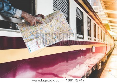 Young asian man holding travel map on hand and pointing in the map asking for direction. Travel direction search lost find a way concept.