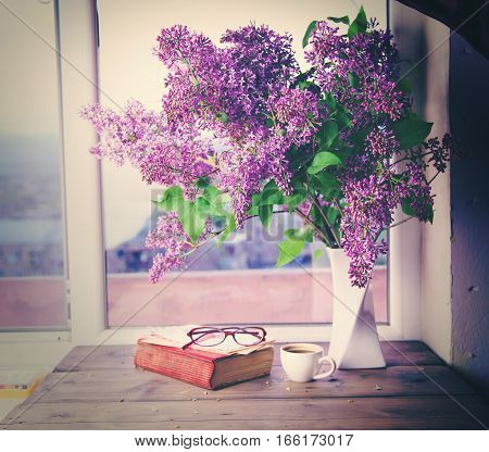 lilac book and cup of coffee on wooden table