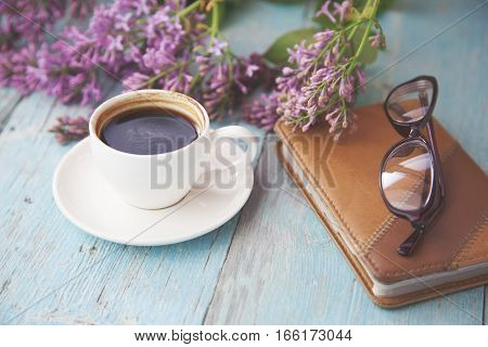 lilac notepad and coffee on wooden table