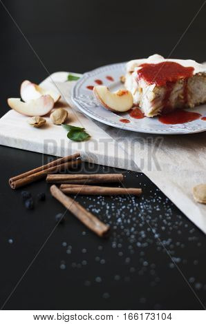 Piece of cake with jam and peaches on a dark wooden table. Pie Baking Cinnamon Peach Jam