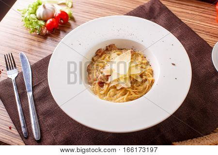 spaghetti al dente with parmesan on a white plate