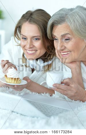 Portrait of senior woman with her adult daughter eat tasty cake, dring tea and watching something on laptop