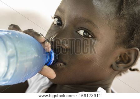 Poverty Symbol: African Black Girl Drinking Heathy Fresh Water. Poverty Symbol in Mali: African Black Girl Drinking Heathy Fresh Water from a bottle.