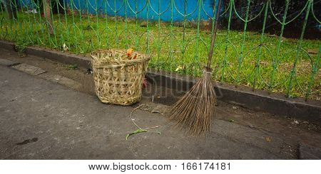 trash basket bag with broom with a grass as background photo taken in pasar minggu jakarta Indonesia java