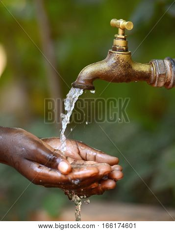 Water Scarsity Symbol - Drinking for African Children. Water Climate Change Symbol: Handful Of Water Scarcity for Children Symbol. Hands Cupped under a Tap to collect water for an African girl. It is the lack of sufficient available water resources.