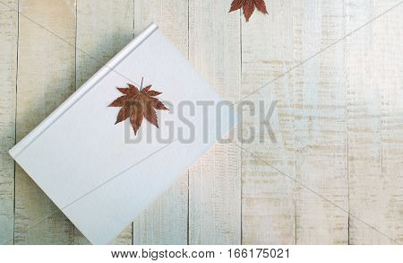 Maple leaf on the white book The book on wooden
