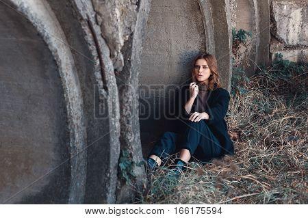 young beautiful woman in black casual coat. Beautiful sad girl outdoors. Fashion portrait of beautiful stylish brunette woman on grunge concrete background