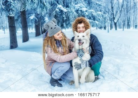 happy winter couple with pet white dog. Young man and woman in love with dog walking in the snowy forest. Family playing with dog outdoor