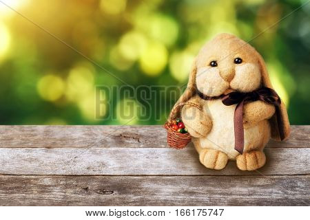 Easter bunny toy with basket of decorated eggs on wooden table over spring bokeh. Easter decoration rabbit. Easter card