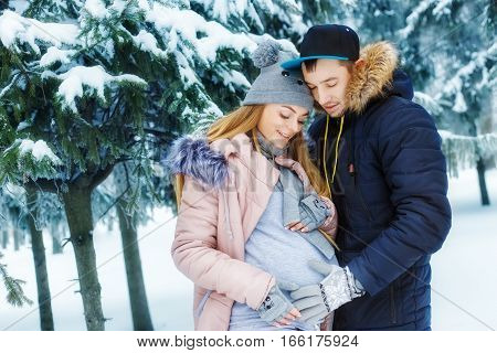Pregnant couple in winter forest. Expectant mother and her husband waiting for baby in winter. Love, family, pregnancy concept. Future parents walking outdoor. Happy family. Man holding pregnant belly
