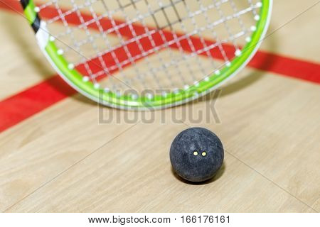 Close up of a squash racket and ball on the wooden background. Racquetball equipment on the floor of court. Photo with toning and selective focus. Squash time