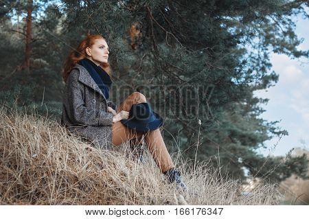Beautiful red-haired woman. Redhead woman weared knitted scarf, coat, floppy hat in the forest. Portrait of dreaming woman with curly red hair and blue eyes posing outdoors