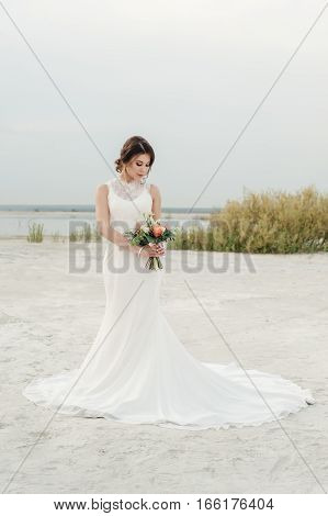 Beautiful bride in a wedding dress with a bouquet in his hand standing in the sand on the shore of the lake