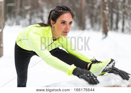 Winter training Fitness model athlete girl warm up stretching her hamstrings, leg and back