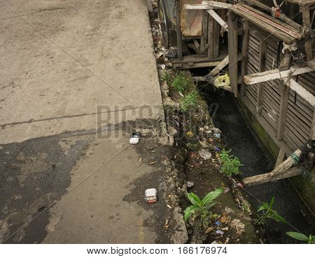 A dirty bamboo bench lay on top of dirty and stinky ditch photo taken in Jakarta indonesia java