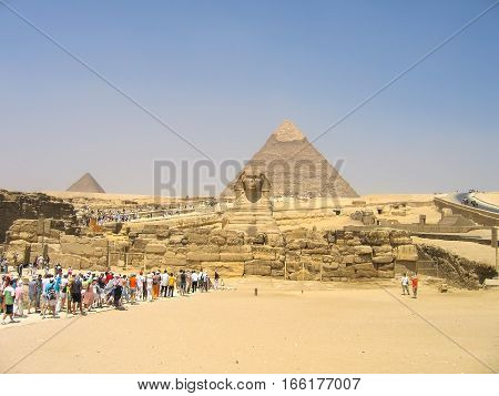 Giza, Egypt - June 30, 2008: Tourists linining up to see the Sphynx statue and great pyramids