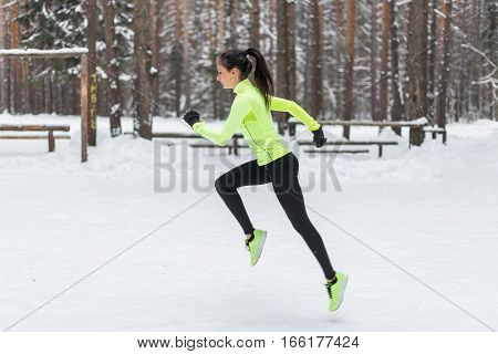 Athlete woman runner running in cold snowing weather. Cardio street training marathon jogging