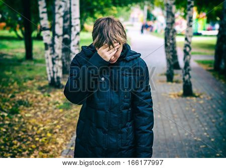 Toned Photo of Sad Teenager stand in the Autumn Park