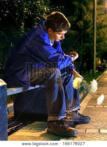 Teenager with Flowers sit in the Night Park