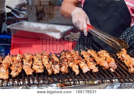 Man cooking chicken skewers kebabs on grill