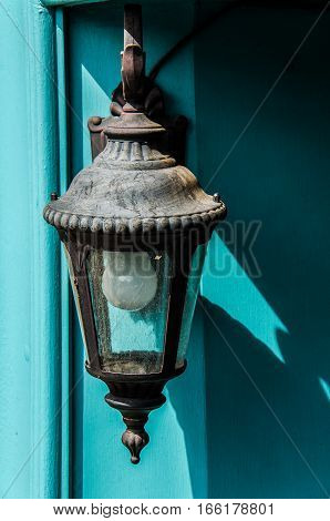 Old antique lantern against turqoise blue door in daylight