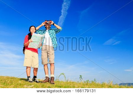 young hiking couple standing at the top of a hill