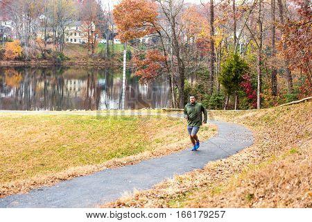 Fairfax, USA - November 24, 2016: Man jogging on trail path by lake Woodglen in Virginia near residential neighborhood