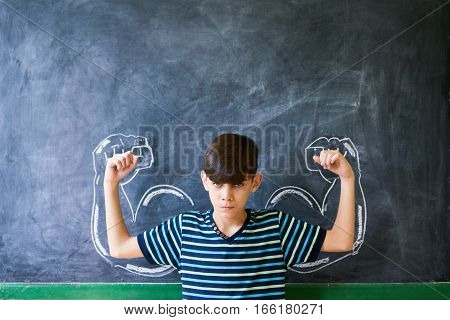 Concepts on blackboard at school. Intelligent and successful latino boy in class standing against blackboard with drawing representing concept of bullying
