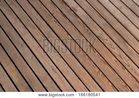 Wooden planks arranged diagonally. Surface of old wooden brown planks arranged on a diagonal suitable for use as background. Wooden wall.