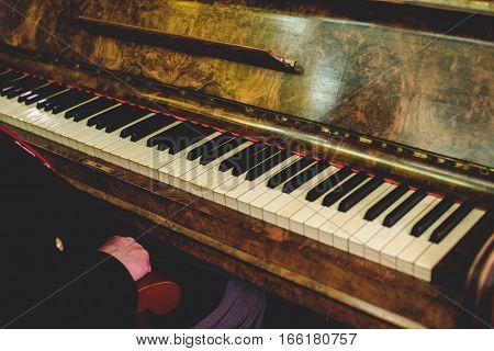 Man sits at an old vintage piano