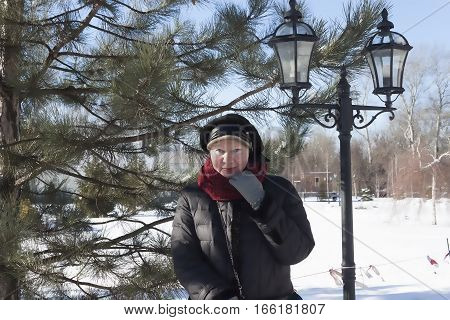 Portrait of smiling senior woman in a snow-covered winter park near lights