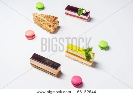 Several pieces of cake and makarons photographed on a white background