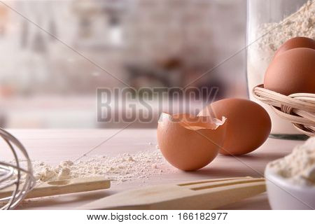 Fresh Eggs And Utensils On Wooden Bench With Kitchen Background