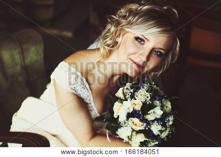 Pretty Blonde Bride Smiles Holding A Wedding Bouquet Near Her Face