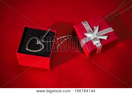 Silver heart pendant in a red gift box over a red satin background