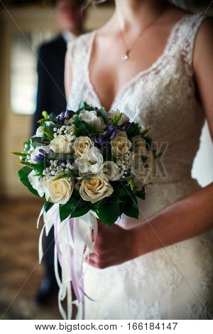 An Elegant Bride In Laces Holds A Bouquet In Her Arms