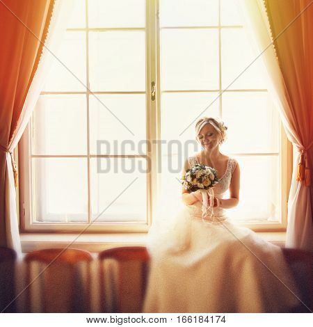 Sunlight Highlights A Bride While She Seats In The Front Of A Big Window